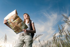 Young woman with map and backpack. Beautiful young woman with backpack and map in hands standing outisde in the field and looking in front of her. Blue cloudy Royalty Free Stock Image