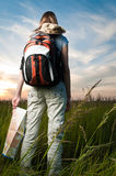 Young woman with map and backpack. Beautiful young woman with backpack and map in hand standing outisde in the field with her back to camera. Sunset cloudy blue Stock Photos