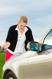Young woman with map on car being lost. Young woman in front of bonnet of a car with map looking for directions, she is lost Royalty Free Stock Photo