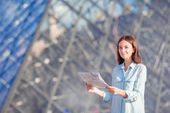 Young woman with map in european city outdoors. Happy young woman with a city map in european city, Paris Royalty Free Stock Photography