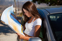 Young woman with map near the car. Young woman stand near the car and look on map Royalty Free Stock Photos