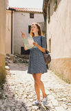 Young woman with a map on the old European streets. Young woman with a map indicating the side on the background of the old European streets. Krk Island, Croatia Stock Image
