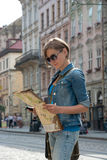 Young woman with a map on the streets of a European city Stock Photo