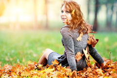 Young woman in maple leaves in autumn park looking at camera. Young happy woman sitting in maple leaves in autumn park looking at camera stock photos