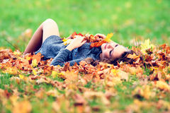 Young woman in maple leaves in autumn park. Young woman lying down in maple leaves in autumn park royalty free stock photography