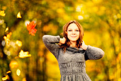 Young woman in maple leaves in autumn park. With raised arms royalty free stock photos