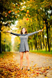 Young woman in maple leaves in autumn park. With raised arms stock photos