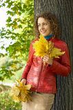 Young woman with maple leaves near tree in autumn. Young woman with maple leaves in hands near tree in wood in autumn royalty free stock image