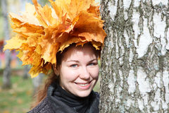 Young woman with maple standing near birch Royalty Free Stock Photography