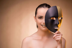 The young woman with mask in carnival concept. Young woman with mask in carnival concept Stock Photo