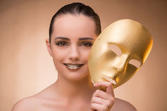 The young woman with mask in carnival concept. Young woman with mask in carnival concept Royalty Free Stock Photo