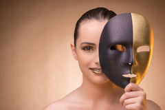 The young woman with mask in carnival concept. Young woman with mask in carnival concept Royalty Free Stock Images