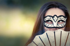 Young Woman with Mask and Fan Royalty Free Stock Photos