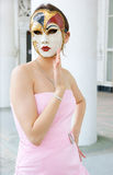 Young woman with mask in pink dress Stock Photos