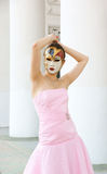 Young woman with mask in pink dress