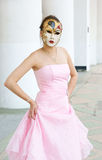 Young woman with mask in pink dress Stock Images