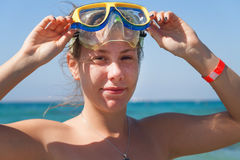 A young woman in a mask for scuba diving laughs, a large portrait. The concept of a hilarious and excellent holiday on the beach royalty free stock photography