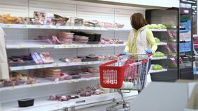 Young woman in mask with shopping cart walking by meat shelves at grocery store