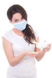 Young woman in mask showing with bottle of pills isolated on whi Royalty Free Stock Photo