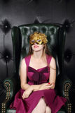 Young woman in mask sits in leather armchair Royalty Free Stock Images