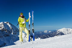 Young woman in mask stands and holds ski, poles. Young woman in mask standing and holding ski and ski poles during sunny winter day on Krasnaya polyana ski Stock Images