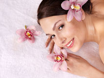 Young woman on massage table in beauty spa. Stock Photos