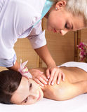 Young woman on massage table in beauty spa. Stock Photo