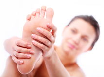 Young woman massages her foot. Royalty Free Stock Photography