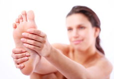 Young woman massages her foot. Stock Images