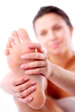 Young woman massages her foot. Stock Photos