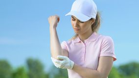 Young woman massaging bruised elbow after golf tournament, professional injury stock footage