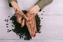 Young woman massaging a hand with coffee scrub stock images