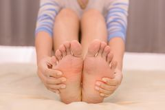 Young woman massaging her feet on the bed., Healthcare Royalty Free Stock Images