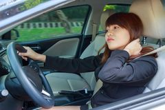 Young woman massaging her neck or shoulder while driving a car a royalty free stock photography