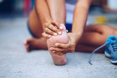 Young woman massaging her painful foot from exercising. And running Stock Photos