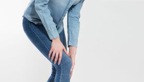 A young woman massaging her painful knee, suffering girl : joint pain.  stock photography
