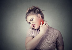 Young woman massaging her painful neck colored in red Royalty Free Stock Images