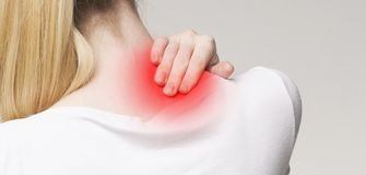 Young woman massaging her sore neck, panorama stock photo