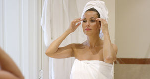 Young woman massaging her temples. With her fingertips as she stands in front of a mirror in a bathroom wrapped in a white towel stock photos