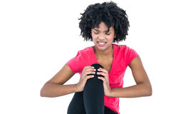 Young woman massaging knee Stock Images