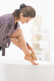 Young woman massaging leg in bathroom Stock Photography