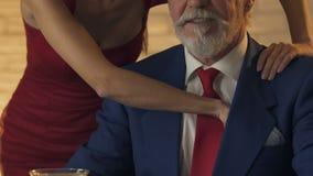 Young woman massaging shoulders of old man, stealing golden card, closeup
