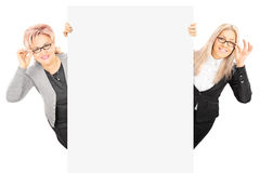 Young woman and mature lady with glasses standing behind panel Royalty Free Stock Photos