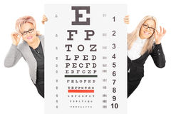Young woman and a mature lady standing behind eyesight tes. Young women and a mature lady with glasses standing behind eyesight test isolated on white background stock images