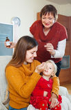 Young woman with mature mother giving  syrup to unwell toddler. Young women with mature mother giving  syrup to unwell toddler at home Stock Images