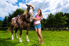 Young woman on the meadow with horse Stock Images