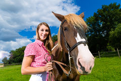 Young woman on the meadow with horse Royalty Free Stock Images