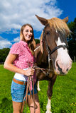 Young woman on the meadow with horse Royalty Free Stock Image