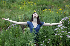 Young woman in meadow with outstretched arms Royalty Free Stock Image