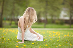 Young woman on meadow. A young woman sitting on the grass on a meadow Stock Images